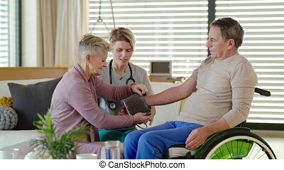 Healthcare worker visiting senior patient in wheelchair at ...