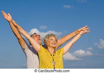 healthy active christian senior couple arms raised in praise