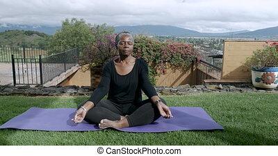 Healthy African American senior sitting cross legged...