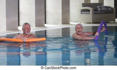 Healthy aging couple doing aqua aerobics in pool - Active...