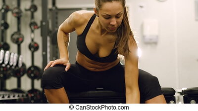 Healthy and focsued woman lifts weights at fitness gym -...