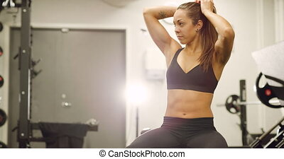 Healthy and focused woman lifts weights at fitness gym -...