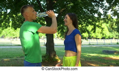 Healthy athletic man drinking water after running