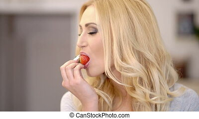 Healthy attractive blond woman eating a strawberry