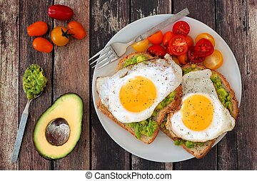 Healthy avocado, egg open sandwiches on a plate with cherry...