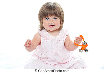 Healthy baby girl sitting on floor playing with rattle