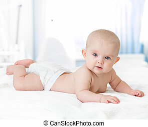 healthy baby lying on bed in bedroom