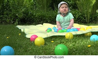 healthy baby spent time between colorful balls on plaid in...