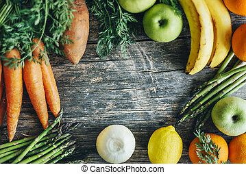 Healthy bio food ingredients frame background from above. Top view of organic superfood border on rustic wooden table. Colorful fruits and vegetables overhead.