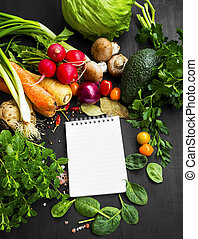 Healthy bio vegetables and spices with recipe notebook in the middle , overhead shot