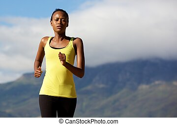 Healthy black woman running outdoors in nature