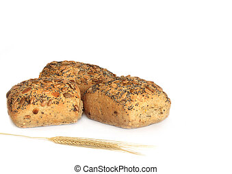 Multi grain stone baked bread rolls covered in sunflower seeds, linseeds, ground buckwheat and millet with an ear of wheat in the foreground. Over white background.