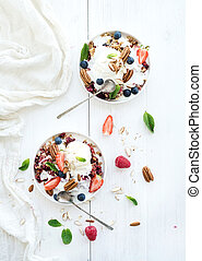 Healthy breakfast. Berry crumble with fresh blueberries, raspberries, strawberries, almond, walnuts, pecans, yogurt, and mint in ceramic plates over white wooden surface