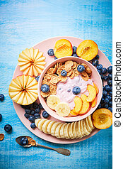 Top view of Super Healthy breakfast bowl: berry greek yoghurt with fresh blueberries, peach, banana and flakes in the pink bowl on the blue wooden table.
