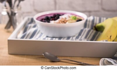 Healthy breakfast bowl: blueberry smoothie with banana,...