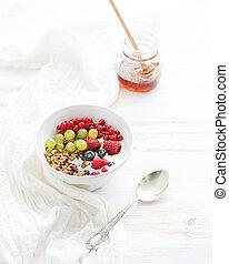 Healthy breakfast. Bowl of oat granola with yogurt, fresh berries and honey.