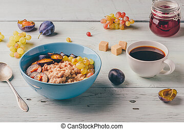 Porridge with fresh plum, green grapes and cup of coffee.