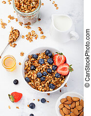 Healthy breakfast Fresh granola, muesli in bowl with milk and berries Top view