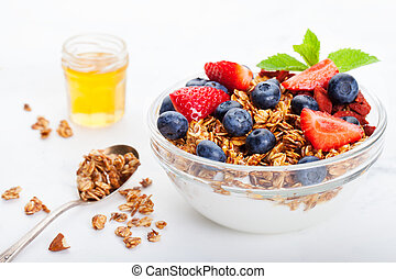 Healthy breakfast Fresh granola, muesli in bowl with milk and berries White background