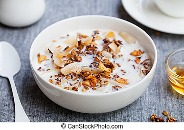 Healthy breakfast. Fresh granola, muesli with milk in a white bowl on grey textile background.