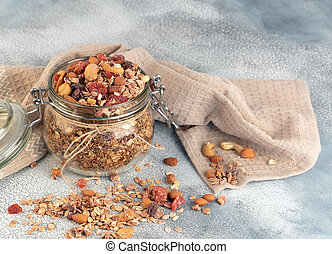 Healthy breakfast - glass jars of oat flakes, granola with dried fruit, berries and nuts on light background