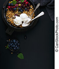 Healthy breakfast. Oat granola crumble with fresh berries, seeds, ice-cream and mint leaves in iron skillet pan on dark wooden board over black backdrop, top view, copy space