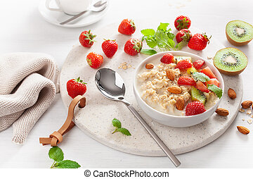 healthy breakfast oatmeal porridge, strawberry, nuts