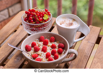 Healthy breakfast: oatmeal with fresh berries in a bowl with a cup of coffee
