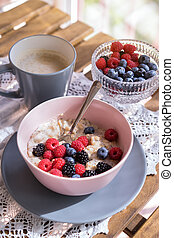 Healthy breakfast - oatmeal with fresh berries in a bowl with a cup of coffee