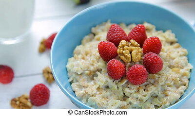 healthy breakfast - oatmeal with fresh, ripe raspberries and walnuts in a bowl standing on a wooden table. Close up