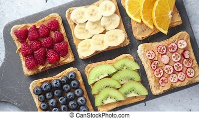 Wholegrain bread slices with peanut butter and various...