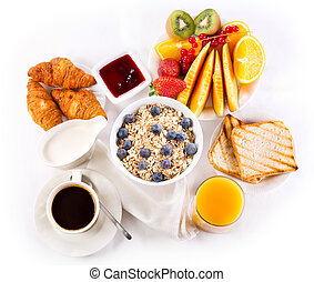 healthy breakfast with bowl of muesli, coffee, croissants, juice and fruits