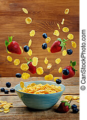 Healthy breakfast with flying corn flakes, strawberries and blueberries