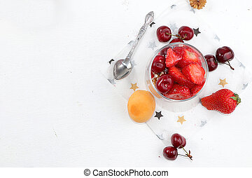 Healthy breakfast with ingredients, food for children, yogurt with granola, strawberries, cherries and peaches on a light table. The concept of healthy and natural food, lifestyle. selective focus