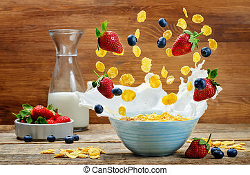 Healthy breakfast with milk, flying corn flakes, strawberries and blueberries
