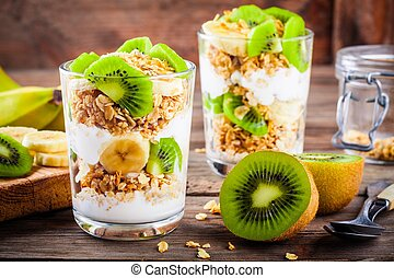 Healthy breakfast: yogurt parfait with granola, banana and kiwi