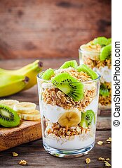 Healthy breakfast: yogurt parfait with granola, banana and kiwi