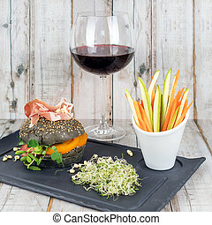 Healthy burger with hamon, tomatoes, micro greens and black wholegrain buns, vegetable sticks and red wine on black slate board over wooden background. Clean eating, dieting, detox food concept