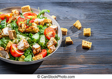 Healthy Caesar salad made of fresh vegetables on blue table