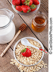 Healthy cereal with milk, honey and strawberry