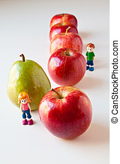 Toy girl and boy overwhelmed by making good food choices. Green pear standing out from a line of red apples. Concepts: being different, unique, stick out, being singled out, healthy choices, good nutrition