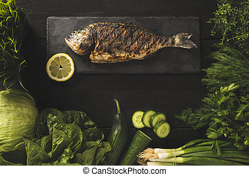 Bream fish on a black stone with green vegetables