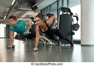 Healthy Couple Doing Exercise With Dumbbells