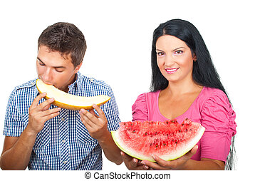 Healthy couple eating melons