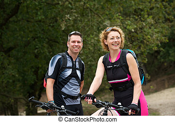 Healthy couple smiling with bicycles