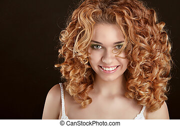 Healthy Curly Hair. Attractive smiling woman portrait on black background