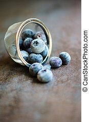 Fresh organic blueberries covered with frost in the bowl on the vintage stone table