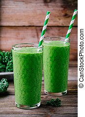 Healthy detox green smoothie with kale in a glass on wooden background