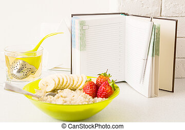 Healthy diet planning concept with open notebook in focus and plate of porridge