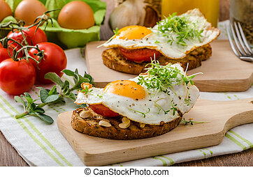 Healthy dinner - a panini garlic toast with fried egg, peanuts and tomatoes, sprinkled microgreens
